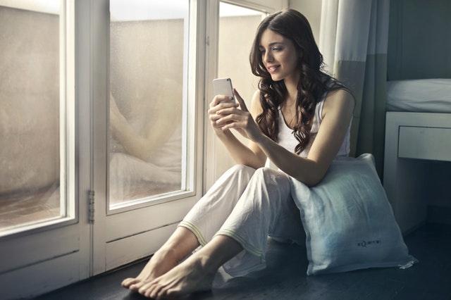 žena s mobilem u okna