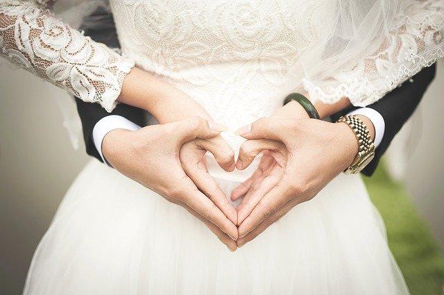 Svatební fotografie muž a žena s prsty do tvaru srdce.
