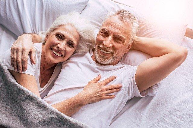 Manželský pár v důchodovém věku ležící v posteli.